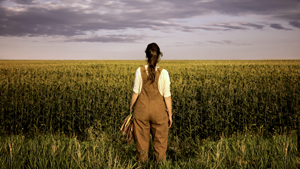 photo of a woman standing in a field
