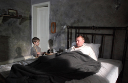 photo of a young boy talking to a man laying in bed