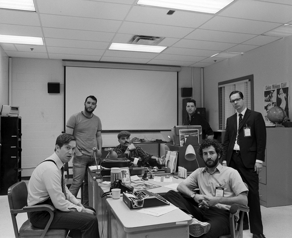 photo of six men sitting and standing around an office desk