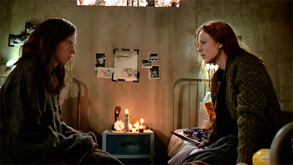 photo of two young women sitting face to face across from each other