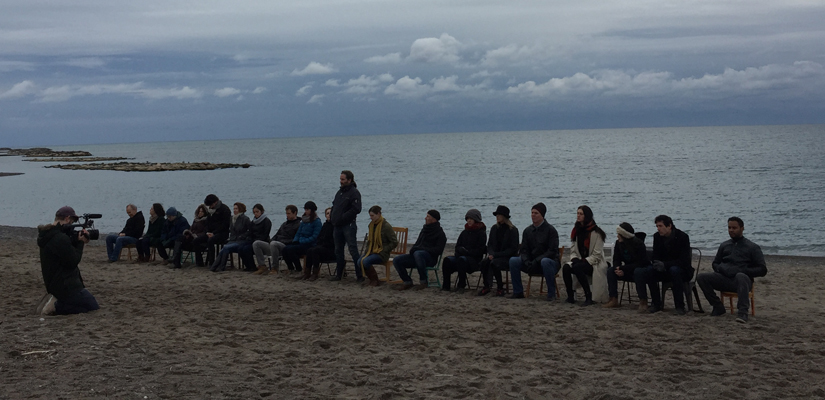 photo of a photographer facing a line of people sitting in chairs on a beach