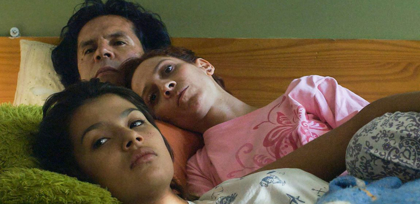 photo of a man and two women laying in a bed.