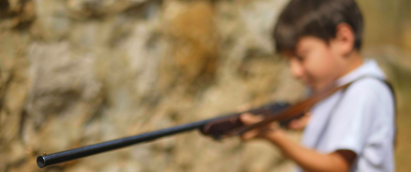 blurred photo of a young boy with a rifle